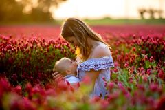Den härliga barnmodern som ammar hennes litet barn, behandla som ett barn pojken går in Royaltyfria Bilder
