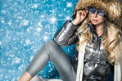 Den härliga bedöva kvinnan med långt blont hår och gör perfekt iklädda vinterkläder för framsidan, det varma omslaget för silver, Arkivbilder