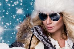 Den härliga bedöva kvinnan med långt blont hår och gör perfekt iklädda vinterkläder för framsidan, försilvrar det varma omslags-  Royaltyfri Foto