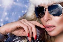Den härliga bedöva kvinnan med långt blont hår och gör perfekt iklädda vinterkläder för framsidan, försilvrar det varma omslags-  Royaltyfri Fotografi