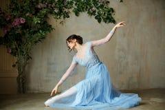 Den härliga behagfulla flickaballerina i blått klär och pointeskor royaltyfria foton