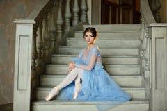 Den härliga behagfulla flickaballerina i en blå klänning och pointe är royaltyfri fotografi