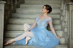 Den härliga behagfulla flickaballerina i en blå klänning och pointe är royaltyfria foton