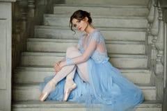 Den härliga behagfulla flickaballerina i en blå klänning och pointe är arkivbild