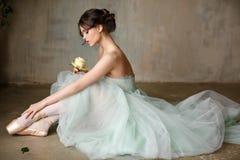 Den härliga behagfulla flickaballerina i en luftklänning och pointe sitter royaltyfria foton