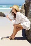 Den härliga benägenheten för ung kvinna mot vaggar på stranden Royaltyfria Bilder