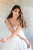 Den härliga biracial tonåriga flickan i den vita klänningen som sitter beväpnar crosse Fotografering för Bildbyråer