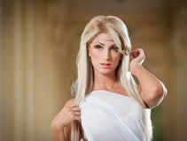 Den härliga blonda ängeln med ljus vit påskyndar, och vit skyler att posera som är utomhus- Fotografering för Bildbyråer
