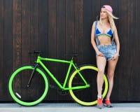 Den härliga blonda flickan i bikini- och grov bomullstvillkortslutningar som poserar med den trendiga cykeln, fixar Fotografering för Bildbyråer