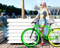 Den härliga blonda flickan i bikini- och grov bomullstvillkortslutningar som poserar i stad, parkerar med den trendiga cykelknipa Royaltyfri Bild