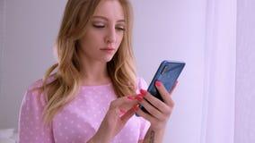Den härliga blonda flickan i en rosa T-tröja av det europeiska utseendet meddelar vid telefonen på fönstret i det ljust stock video