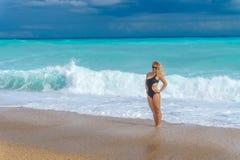 Den härliga blonda flickan i en svart bikini kopplar av på en tom karibisk strand Royaltyfri Bild
