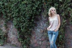 Den härliga blonda flickan i en väst och jeans står den near väggen med vinrankan på stadsgator Arkivfoto