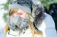 Den härliga blonda flickan i hatt och tumvanten täcker hans framsida utanför i förkylningen arkivfoto