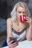 Den härliga blonda flickan i hem- kläder använder en smartphone Royaltyfri Foto
