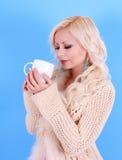 Den härliga blonda flickan i pullover med kuper av kaffe, över blått Arkivbild