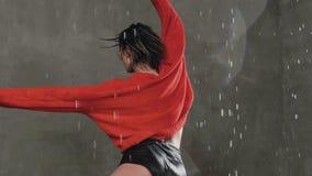 Den härliga blonda flickan i röd tröjadans under dropparna av regn i studion mot bakgrunden av en grå färg lager videofilmer