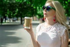Den härliga blonda flickan i staden dricker kaffe Gatafotoperiod Grå kopp med ett vitt lock och ett ställe för logoen royaltyfria bilder