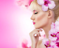 Den härliga flickan med blommor och görar perfekt makeup Royaltyfria Bilder