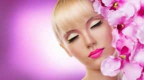 Den härliga blonda kvinnan med blommor och görar perfekt makeup Arkivfoto