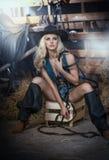 Den härliga blonda flickan med landsblick, sköt inomhus i stallet, lantlig stil Attraktiv kvinna med den svarta cowboyhatten och  Arkivbild