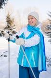 Den härliga blonda flickan med skidar poler i händer under ett kort vilar arkivbilder