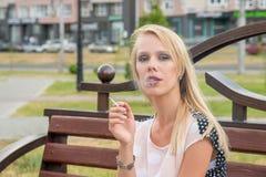 Den härliga blonda flickan röker en vitcigarett utomhus i en cit royaltyfri fotografi