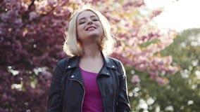 Den härliga blonda flickan ser höger in mot kameran, älskvärda leenden och trycker på hennes hår Härliga sakura, körsbär stock video