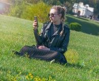 Den härliga blonda flickan sitter på en grön gräsmatta och ser i en smartphone Fotografering för Bildbyråer