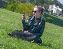 Den härliga blonda flickan sitter på en grön gräsmatta och ser i en smartphone Royaltyfri Foto