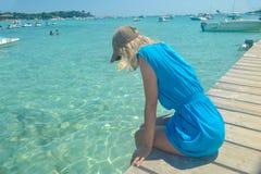 Den härliga blonda flickan sitter på pir och ser turkosvattnet royaltyfria foton