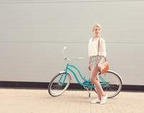 Den härliga blonda flickan står nära tappningcykeln med den bruna tappningpåsen, varmt som tonning Royaltyfri Bild