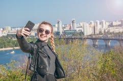 Den härliga blonda flickan står på bakgrunden av staden och gör selfie Royaltyfria Foton