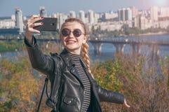 Den härliga blonda flickan står på bakgrunden av staden och gör selfie Arkivfoton