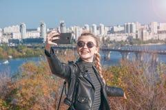 Den härliga blonda flickan står på bakgrunden av staden och gör selfie Royaltyfri Foto