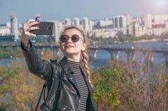 Den härliga blonda flickan står på bakgrunden av staden och gör selfie Royaltyfria Bilder