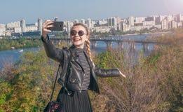Den härliga blonda flickan står på bakgrunden av staden och gör selfie Royaltyfri Bild