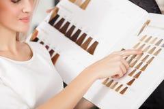 Den härliga blonda flickan väljer färg av royaltyfri foto
