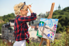 Den härliga blonda kvinnakonstnären målar ett färgrikt Fotografering för Bildbyråer