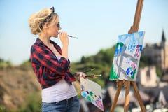 Den härliga blonda kvinnakonstnären målar ett färgrikt Arkivfoton