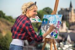 Den härliga blonda kvinnakonstnären målar ett färgrikt Arkivfoto