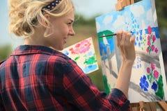 Den härliga blonda kvinnakonstnären målar ett färgrikt Arkivbilder