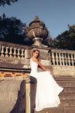 Den härliga blonda kvinnan bär bröllopsklänningen som poserar bredvid den groteska villan Arkivbilder