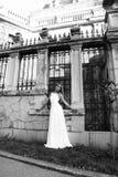 Den härliga blonda kvinnan bär bröllopsklänningen som poserar bredvid den groteska villan Arkivbild