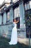 Den härliga blonda kvinnan bär bröllopsklänningen som poserar bredvid den groteska villan Royaltyfria Foton