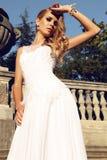 Den härliga blonda kvinnan bär bröllopsklänningen som poserar bredvid den groteska villan Royaltyfria Bilder