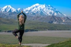 Den härliga blonda kvinnan gör en yoga poserar framme av det Denali berget i Alaska royaltyfria bilder