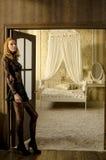 Den härliga blonda kvinnan i elegant snör åt klänningen på dörren till sovrummet fotografering för bildbyråer