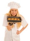 Den härliga blonda kvinnan i kockklänning bakar kakor över Arkivfoton