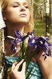 Den härliga blonda kvinnan med blått blommar i en skog Arkivbilder